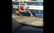 VIDEO | Un bărbat s-a aflat la un pas de moarte după ce a încercat să scoată o mașină blocată de pe calea ferată. Automobilul a fost lovit în plin de tren